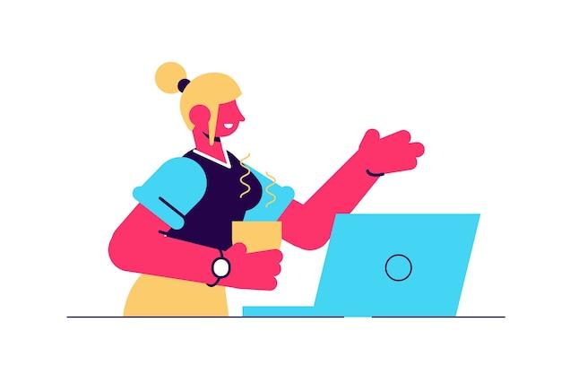 Jonge lachende vrouw die aan tafel op laptop werkt.