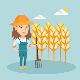 Jonge landbouwer die zich op een gebied met hooivork bevindt.