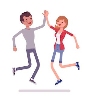 Jonge man en vrouw springen geven hoge vijf