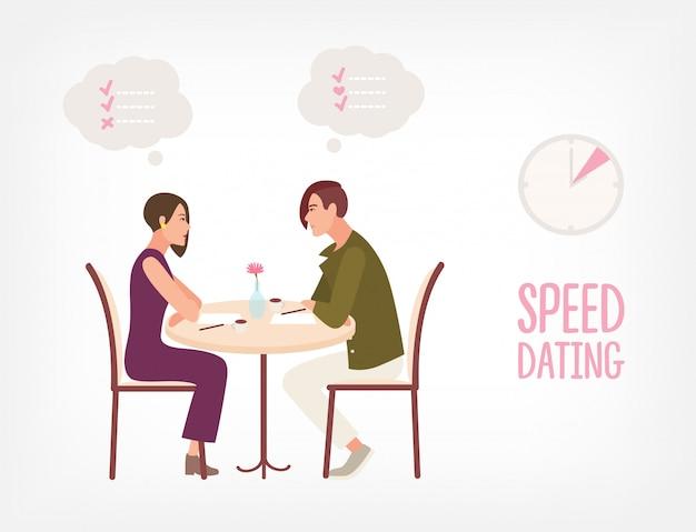 Jonge man en vrouw zitten aan tafel, kijken naar elkaar en praten.