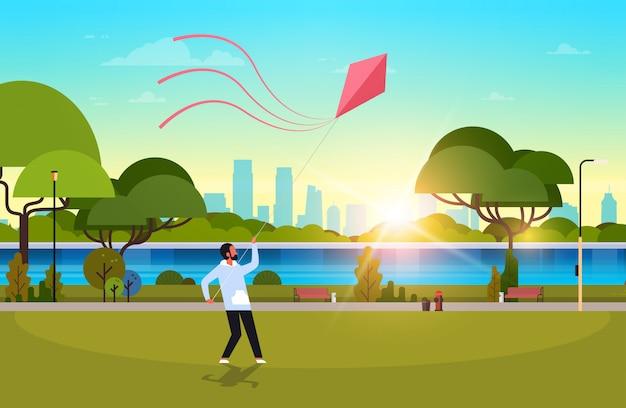 Jonge man lancering vlieger buitenshuis moderne openbare park