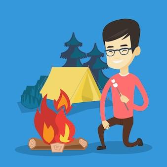 Jonge man marshmallow roosteren boven kampvuur.