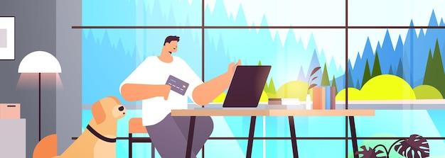 Jonge man met creditcard met behulp van laptop online winkelconcept woonkamer interieur horizontaal portret