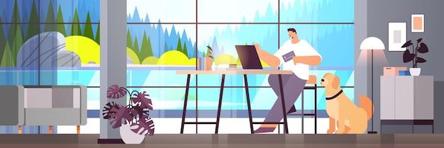 Jonge man met creditcard met behulp van laptop online winkelconcept woonkamer interieur horizontaal volledige lengte