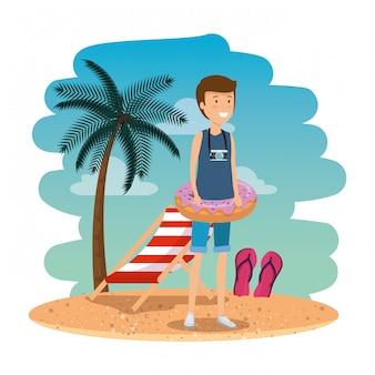 Jonge man met zwembroek en zweven donut op het strand