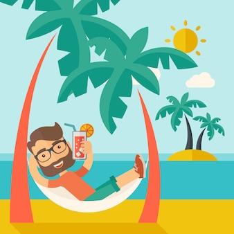 Jonge man op het strand ontspannen en cocktail drinken.