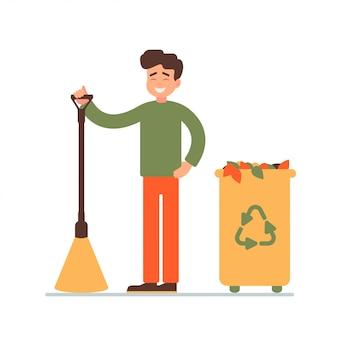 Jonge man verzamelde gevallen bladeren in de vuilnisbak voor recycling