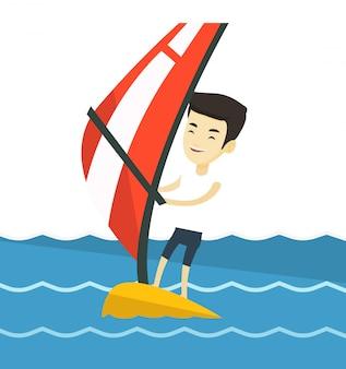 Jonge man windsurfen in de zee.