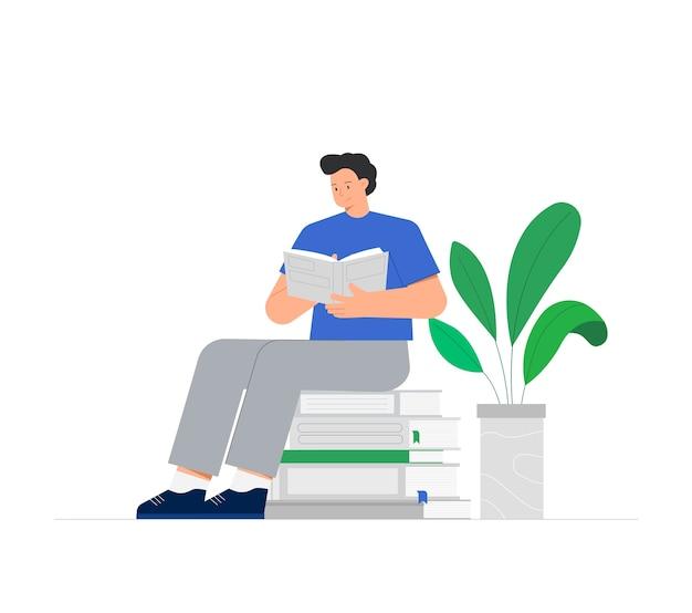 Jonge man zit op een stapel boeken en leest een boek, dichtbij groene bloem in pot.