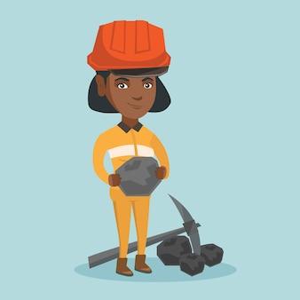 Jonge mijnwerker in bouwvakker die een stuk steenkool houdt.