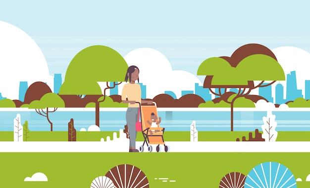 Jonge moeder en pasgeboren babyjongen in wandelwagen wandelen stadspark vrouw duwen kinderwagen met kind