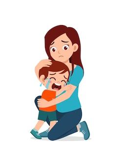 Jonge moeder knuffel huilende kleine jongen en probeer te troosten