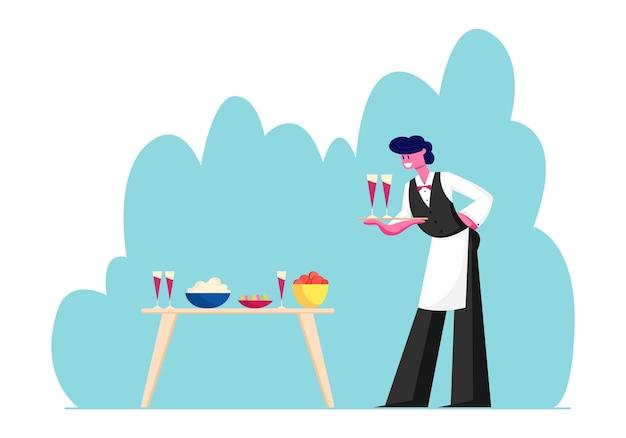 Jonge ober mannelijke karakter in uniform en schort dienblad met paar glazen met rode wijn zet ze op tafel met verschillende gerechten