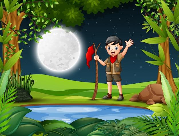 Jonge ontdekkingsreiziger in het bos 's nachts