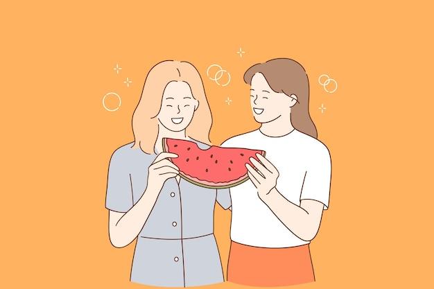 Jonge positieve meisjes staan en genieten van een stuk rijpe sappige watermeloen