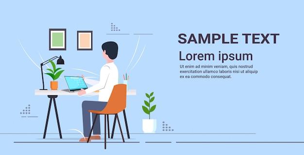 Jonge student zit aan bureau met behulp van laptop schooljongen huiswerk e-learning onderwijs concept volledige lengte achteraanzicht horizontale kopie ruimte