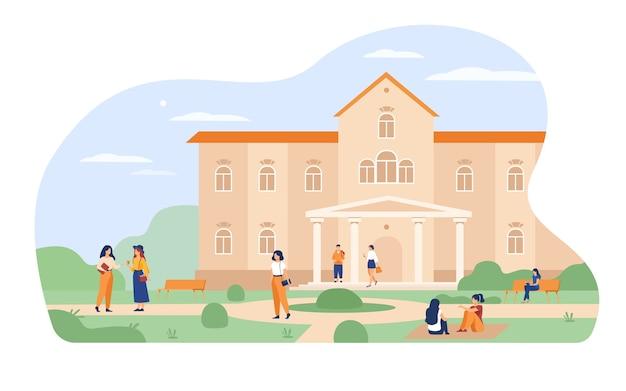 Jonge studenten lopen voor universiteit of hogeschool bouwen platte vectorillustratie. cartoon mensen ontspannen en zittend op het gras op de campus.