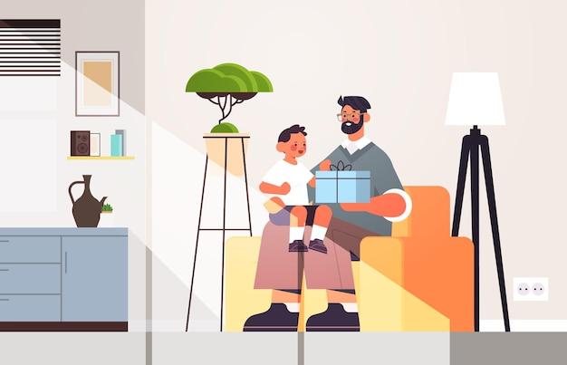 Jonge vader bedrijf geschenkdoos voor zoon ouderschap vaderschap concept vader vakantie cadeau geven aan zijn kind thuis woonkamer interieur horizontaal volle lengte vectorillustratie