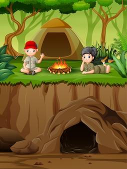 Jonge verkenner die dichtbij vuur op kamp in de zomervakantie geniet van