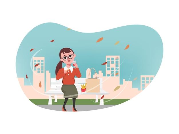 Jonge vrouw die frietjes eet in het park en uitzicht op de stad erachter
