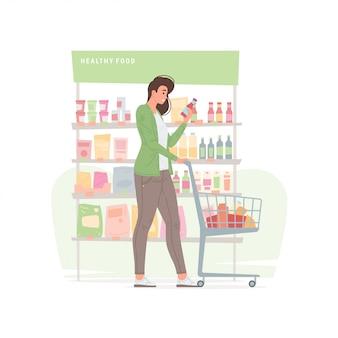 Jonge vrouw die gezond voedsel in supermarkt koopt
