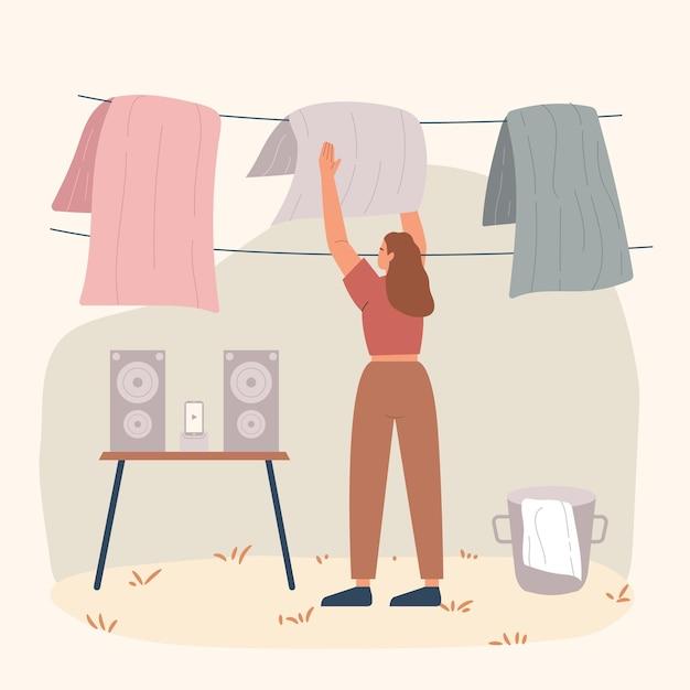 Jonge vrouw die kleren uit emmer neemt & natte kleren uithangt om concept vlakke afbeelding te drogen.