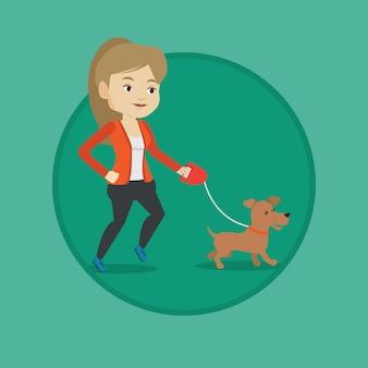 Jonge vrouw die met haar hond loopt.