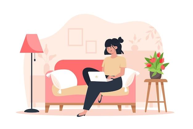 Jonge vrouw die op de bank zit en thuis op een laptop werkt