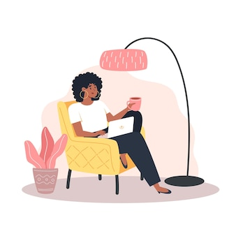 Jonge vrouw die op een fauteuil zit en thuis op een laptop werkt