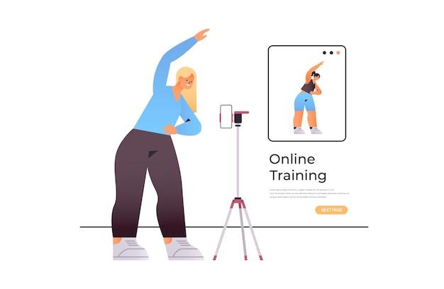 Jonge vrouw doet rekoefeningen tijdens het kijken naar online video trainingsprogramma