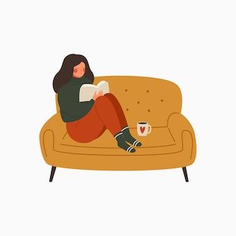 Jonge vrouw gekleed in een warme trui zit op de bank en leest een boek