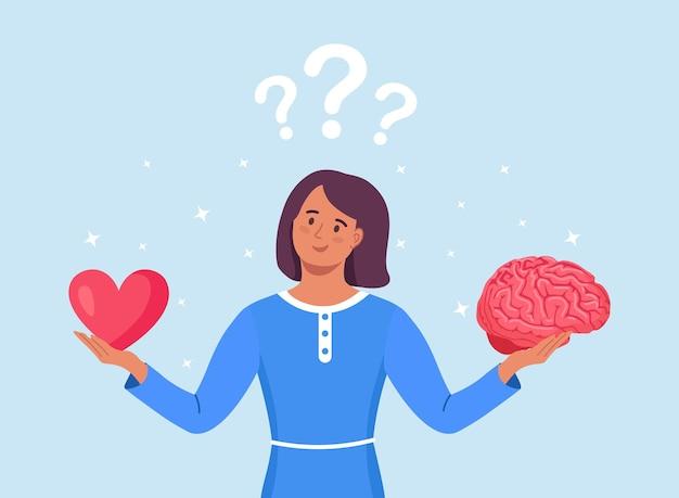 Jonge vrouw houdt hersenen en hart in handen. kiezen tussen gevoel en geest, carrière of hobby, liefde of werk. vrouwelijk personage dat levensbeslissing neemt