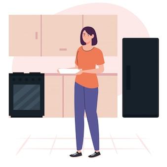 Jonge vrouw koken bedrijf schotel op keukenscène