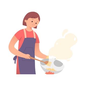 Jonge vrouw koken op een vuur met een koekenpan