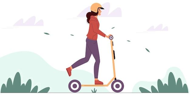 Jonge vrouw met een beschermende helm rijdt op een elektrische scooter in een park milieuvriendelijk voertuig