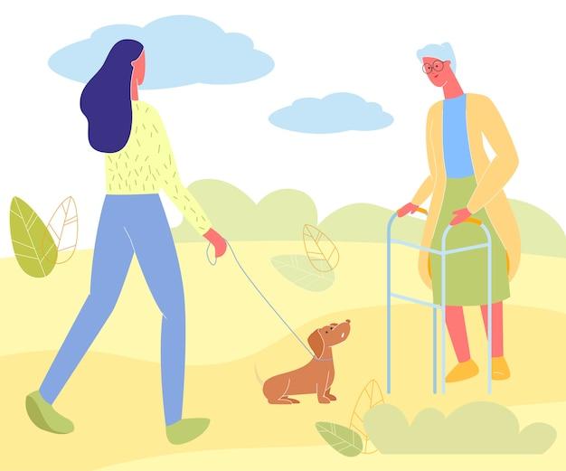 Jonge vrouw met hond en senior dame ontmoeten in park