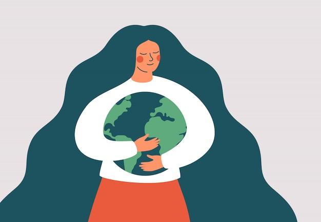 Jonge vrouw omhelst groene planeet aarde met zorg en liefde. aardedag en planeetconcept opslaan.