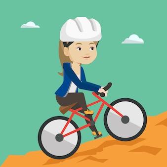 Jonge vrouw op fiets die in de bergen reist.