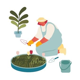 Jonge vrouw tuinman of bloemist werken in de botanische tuin
