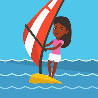 Jonge vrouw windsurfen in de zee.