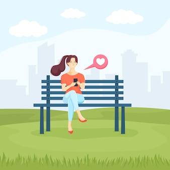 Jonge vrouw zittend in het park op de bank en chatten op smartphone.