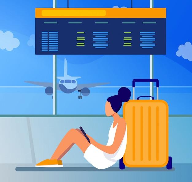 Jonge vrouw zittend op de luchthaven en met behulp van tablet