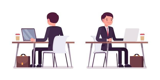 Jonge zakenman die bij de computer, het achter en vooraanzicht werkt