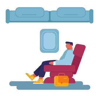 Jonge zakenman zit in comfortabele vliegtuigstoel ontspannen tijdens de vlucht.