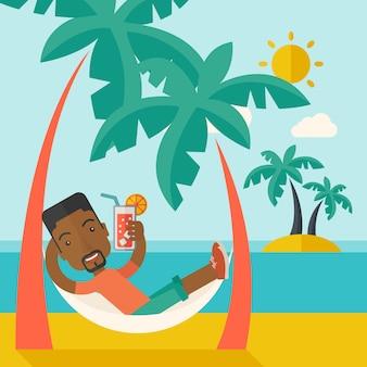 Jonge zwarte man op th strand ontspannen en cocktail drinken.