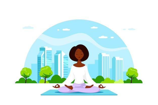 Jonge zwarte vrouw zit in lotus pose met grote stad. beoefening van yoga en meditatie, recreatie, gezonde levensstijl. Premium Vector