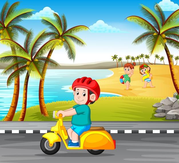 Jongen die de motorfiets op de weg met de strandachtergrond drijft