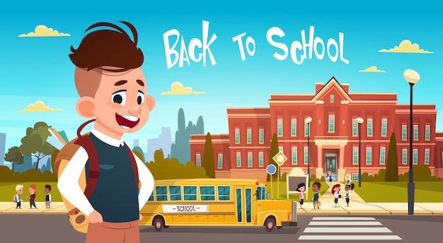 Jongen die naar school over groep van leerlingen gaat die van gele bus lopen