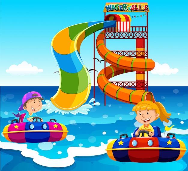 Jongen en meisje die op waterdia berijden in de oceaan