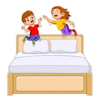 Jongen en meisje springen op het bed